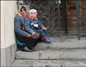 Roma (Gypsy) street beggers crouching to keep warm on the steps of the Russian Orthodox Church in Sofia, Bulgaria.