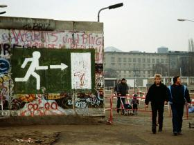 People walk past the former barrier between East and West Berlin after the Fall of Berlin Wall in November 1989.