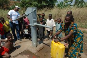 Women and children gather around a communal water pump in Lulimba, Democratic Republic of The Congo.
