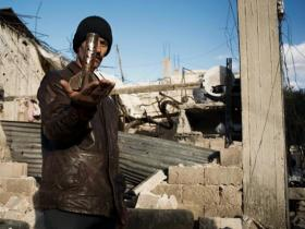 A man displays part of a mortar launched by the Syrian Army that destroyed the house behind him in al-Qsair - February 9, 2012