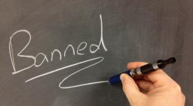 "The image of an electronic cigarette spelling out the word ""BANNED"" on a chalkboard."