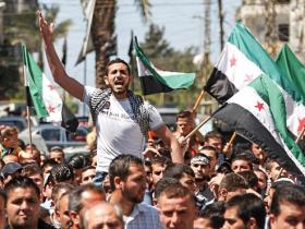 A protester shouts slogans as others wave Syrian opposition flags during a demonstration organized by Lebanese and Syrians living in Lebanon, against Assad and to express solidarity with Syria's anti-government protesters - April 2012.