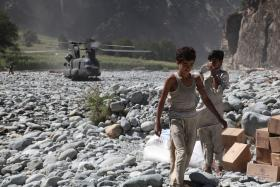 "Pakistani boys unload food from a U.S. Army helicopter. Pakistan needs the United States ""for a whole host of support,"" says Lahore School of Economics professor Shamyla Chaudry."