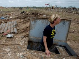 Christie England, an acquisition law paralegal with the 72nd Air Base Wing, based at Tinker Air Force Base, Okla., stands in her storm shelter in front of the remains of her home in Moore, Okla., May 27, 2013, a week after an EF5 tornado with winds exceed