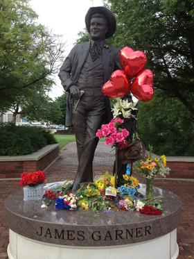 Mourners leave flowers and other mementos at the statue of James Garner in downtown Norman.
