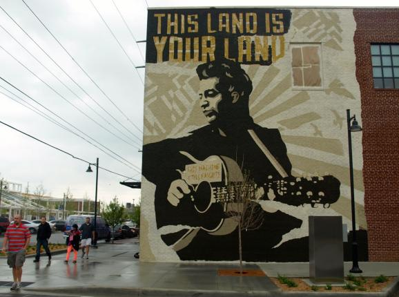 A mural of Woody Guthrie holding his guitar on the side of the Woody Guthrie Center in Tulsa.