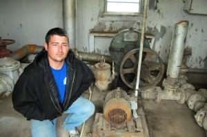 Justin Johnston crouching by sludge pump