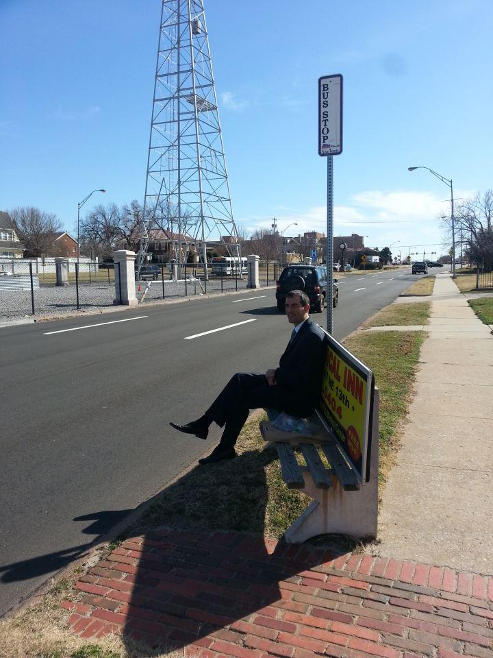 Person on bench at bus stop