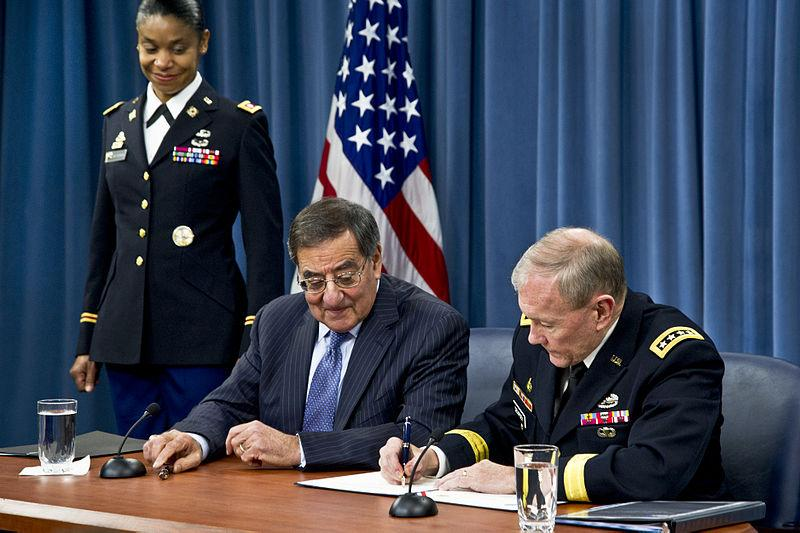 Defense Secretary Leon E. Panetta and Army Gen. Martin E. Dempsey, chairman of the Joint Chiefs of Staff, sign a memo to lift the ban on women in military combat operations during a press conference at the Pentagon, Jan. 24, 2013.