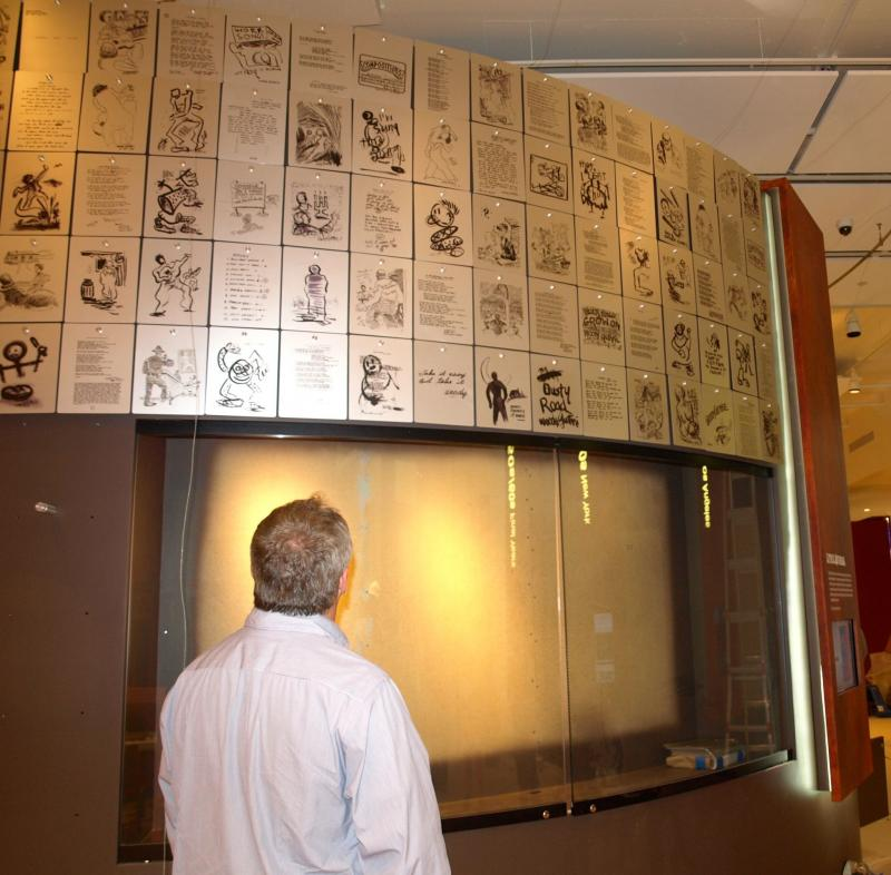 Ken Levit, executive director of the George Kaiser Family Foundation, looks at metal plates etched with lyrics, drawings and doodles by Woody Guthrie.