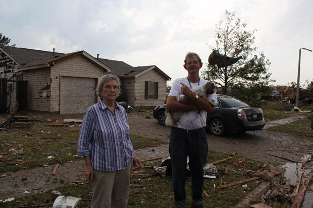 Betty Dupuy and John Switzer stand in front of Switzer's house in a neighborhood devastated by the May 20 tornado in Moore, Okla.