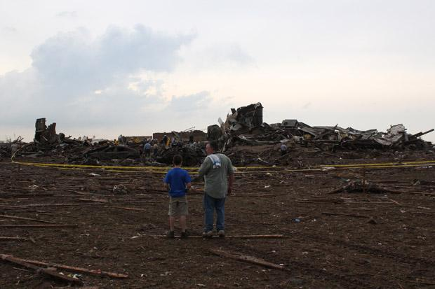 Eleven-year-old Gavin Hawkins and his dad, Joel, stand near the rubble of the Plaza Tower Elementary School. Joel rushed to the school to pick up his son before the storm hit.