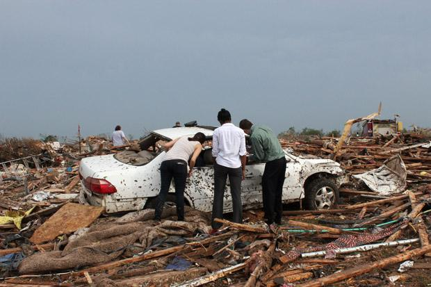 Survivors of May's tornado look at a car damaged in the storm.