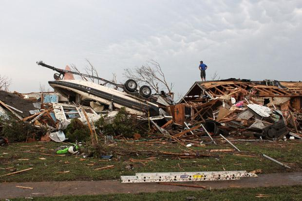 A man on top of a house surveying the tornado damage.