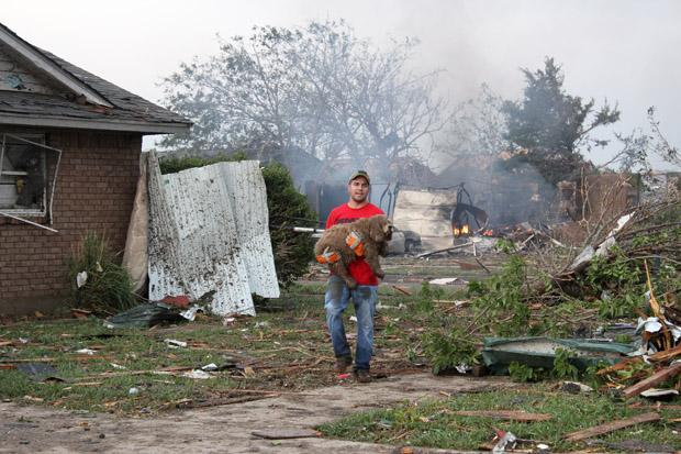 A neighbor carries a soggy, shivering dog away from a pile of rubble.