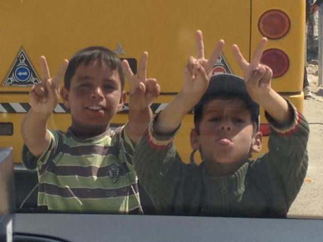 Two Syrian boys pose for peace at the Zaatari refugee camp in Jordan.