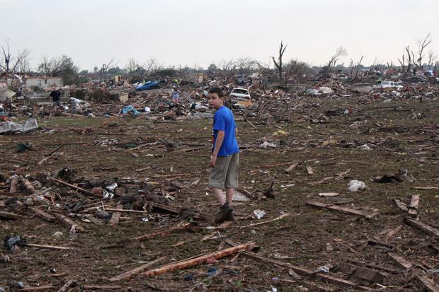 boy walking through rubble