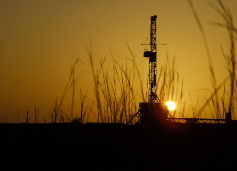 A picture of a natural gas extraction site in the shadow of a setting sun.