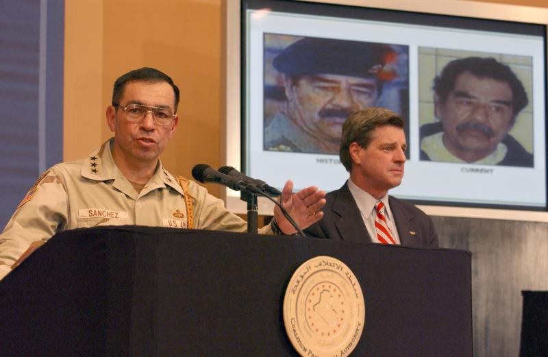 Lt. Gen. Ricardo Sanchez and Amb. L. Paul Bremer speak to the media during a press conference at the Iraqi Forum in Baghdad, covering the capture of Saddam Hussein - December 13, 2003.