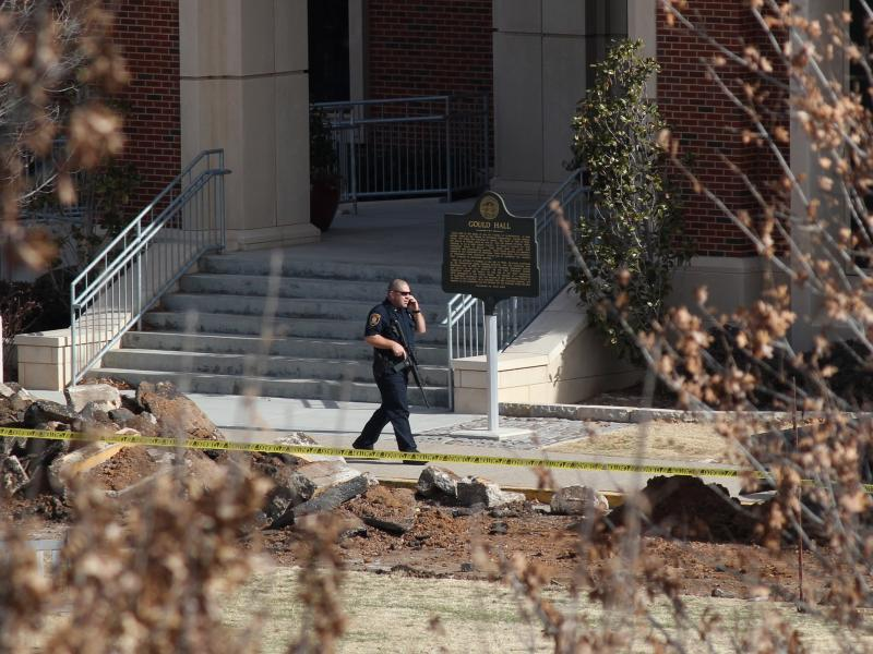 A police officer in front of Gould Hall on the University of Oklahoma campus