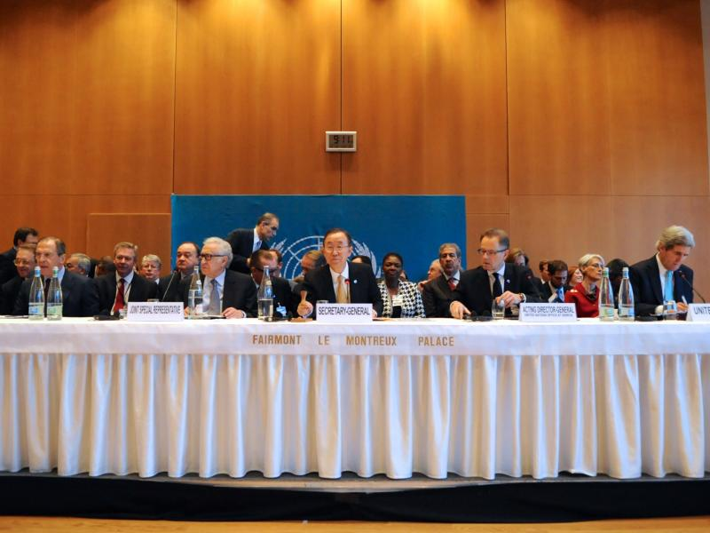 United Nations Secretary-General Ban Ki-moon, flanked by Russian Foreign Minister Sergey Lavrov and U.S. Secretary of State John Kerry, gavels open the Geneva II conference in Montreux, Switzerland, on January 22, 2014.