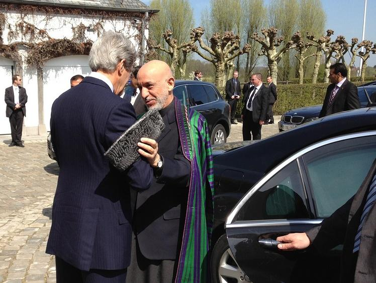 U.S. Secretary of State John Kerry greets Afghan President Hamid Karzai before a trilateral meeting with Pakistani Chief of Army Staff General Ashfaq Kayani in Brussels, Belgium on April 24, 2013.