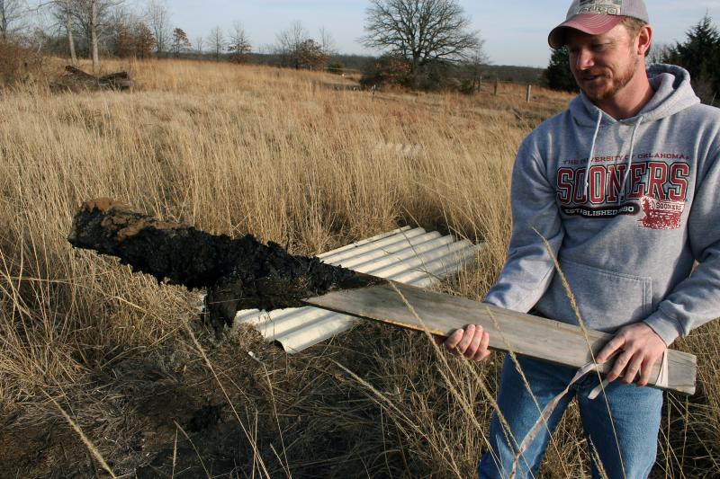 Tyler Lane pulls up a wooden marker covered with oily sludge in the land behind his Bristow home. Lane uses stakes and rope to keep his two children out of the oiliest, most dangerous parts of his property, which sits atop the abandoned Wilcox Refinery, O