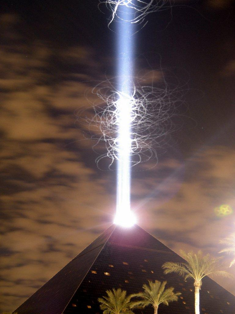 A long exposure nighttime shot of the light above the Luxor Las Vegas hotel, one of the strongest beams of light in the world. The squiggles are either bats or birds swarming around the light, maybe both.