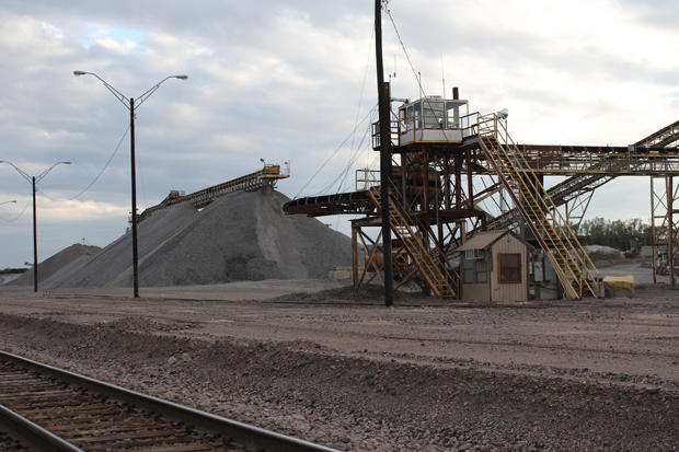 Piles of crushed limestone along railroad tracks near Mill Creek, Okla.