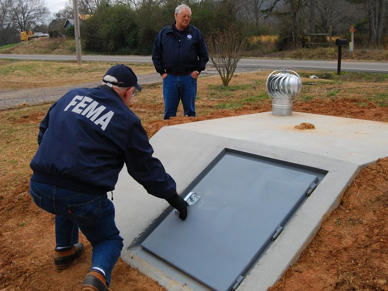 FEMA Public Information Officer, Nate Custer, left, and Resource Manager, Sterling Rich examine a newly installed storm shelter in Arkansas.