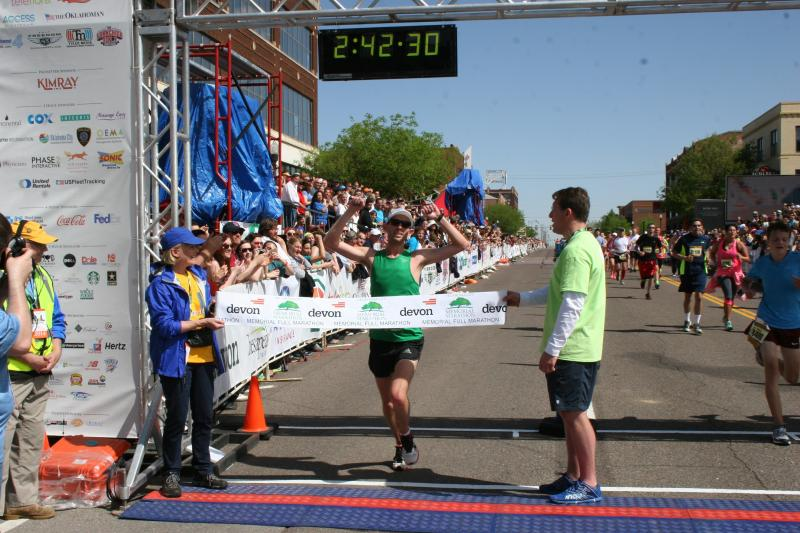 Norman resident Jason Cook crosses the finish line Sunday during the 2014 Oklahoma City Memorial Marathon