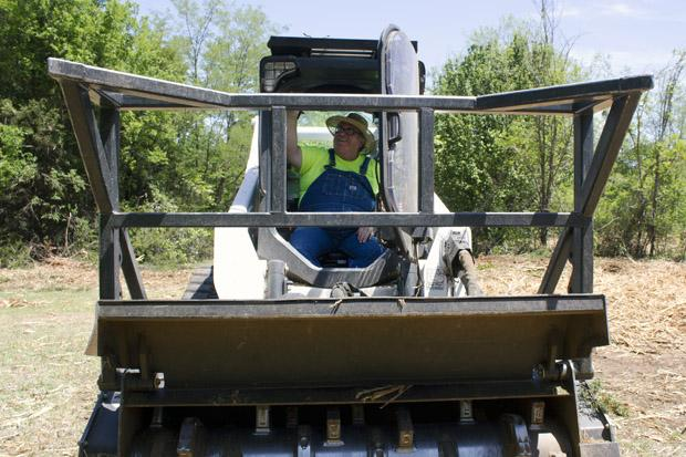 Billy Hays in the cab of a Bobcat, which Oklahoma County modified to cut and shred Eastern Red Cedars.