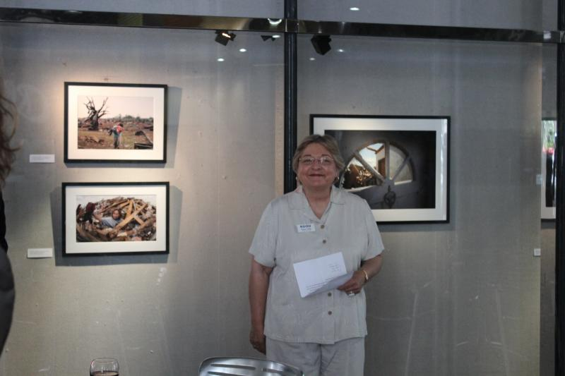 KGOU General Manager Karen Holp stands proud in front of images from Not Another Day in May