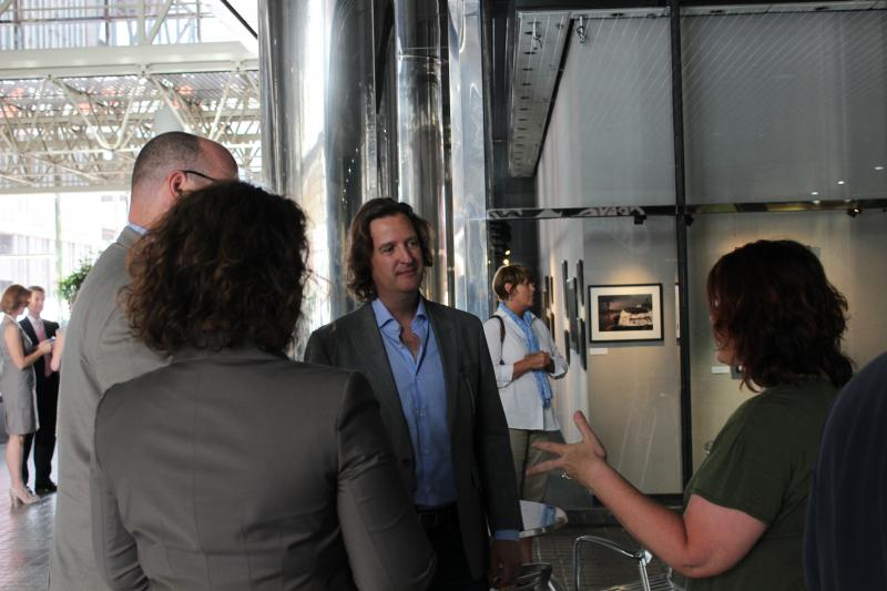 Photography John Nickerson talks to other photographers at Not Just Another Day in May's opening reception