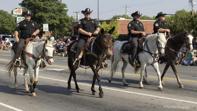 Four policemen ride horses through the 2013 LibertyFest Parade.