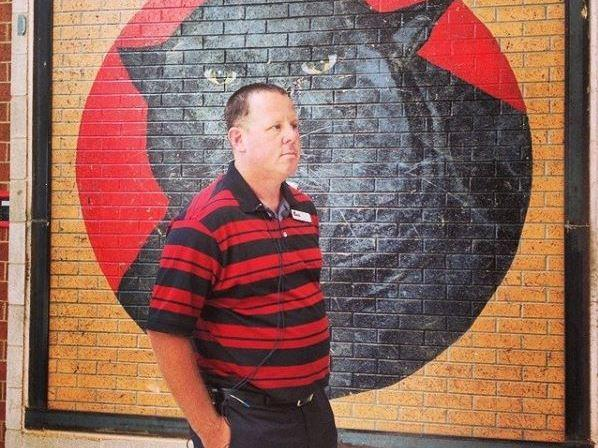 Principal Patrick Chase stands in front of Paws, the school mascot, which is painted on the last remaining piece of wall that stood after a tornado destroyed Plaza Towers Elementary School.