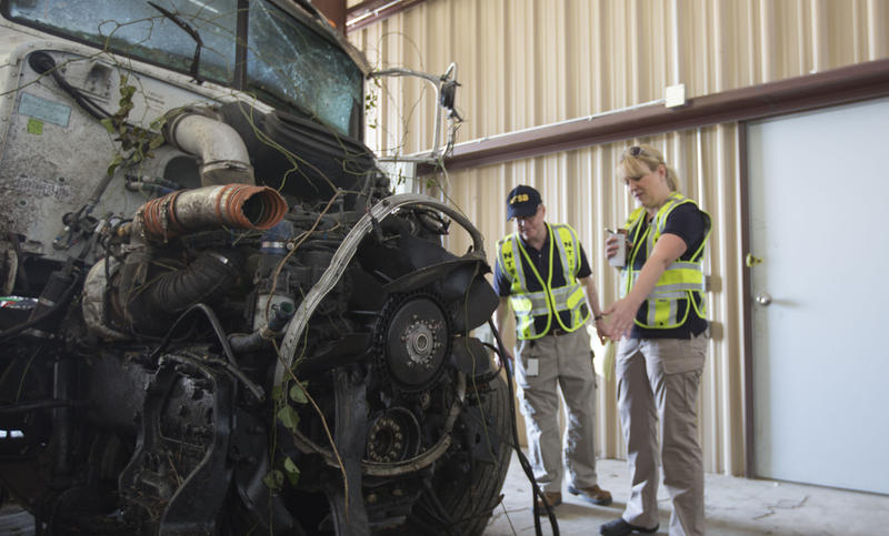 NTSB Board Member Robert Sumwalt and Investigator Jennifer Morrison look at the truck involved in a fatal highway accident in Davis, OK.