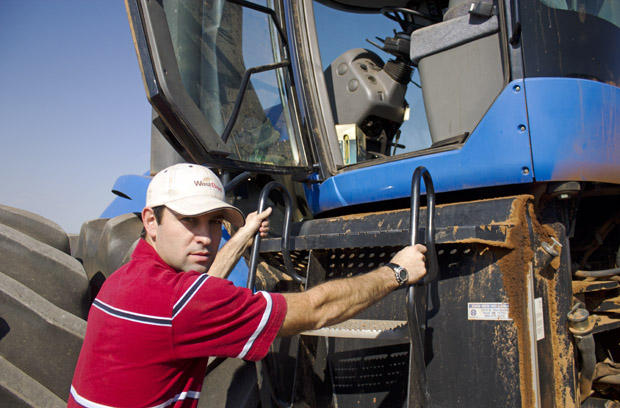 Mason Bolay climbs into the cab of a tractor on his family's farm near Perry, Okla.