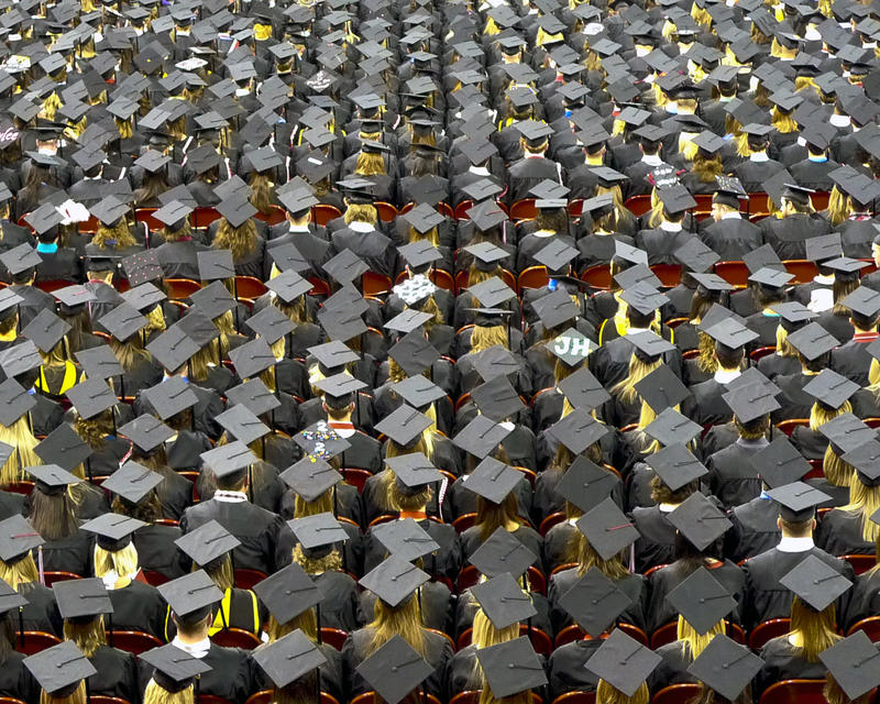 Students in caps and gowns sitting in rows at a graduation
