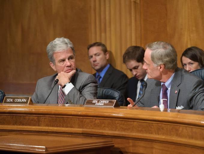 Oklahoma Senator Tom Coburn, the ranking Republican on the Senate Homeland Security and Governmental Affairs Committee, talks with Chairman Sen. Tom Carper (D-Delaware)