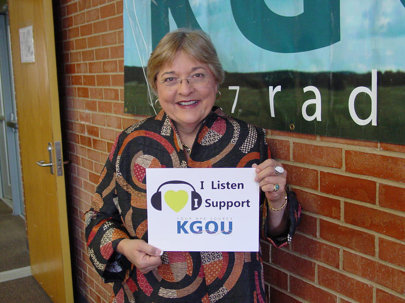 "Karen Holp holds sign that reads, ""I listen, I support KGOU."""