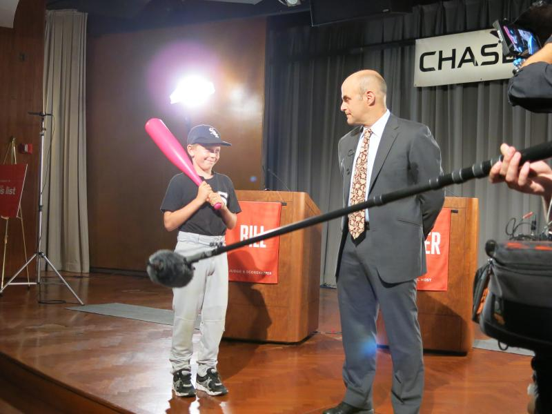 Boy holding bat looks at Peter Sagal