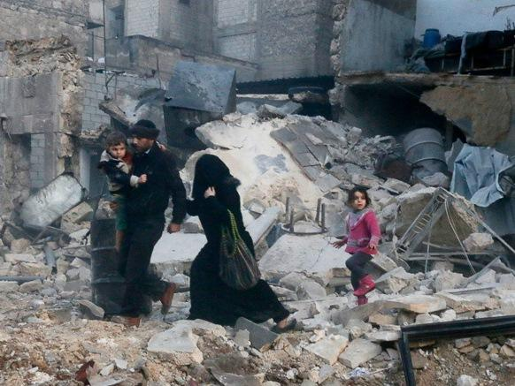 People walk on rubble of collapsed buildings at a site hit by what activists said was barrel bombs dropped by government forces in Aleppo's Dahret Awwad neighborhood January 29, 2014.
