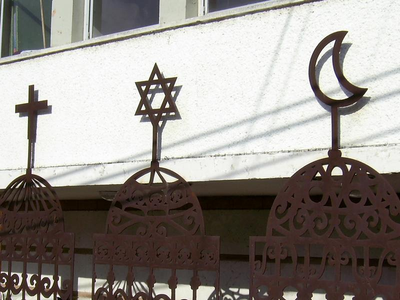 The Jewish Star of David, Arab- Christian Cross and Crescent on the front of Beit Hagefen Arab-Jewish Center in Haifa.