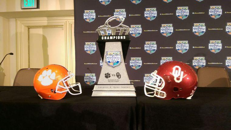 Clemson University football helmet, the Russell Athletic Bowl trophy, and a University of Oklahoma football helmet