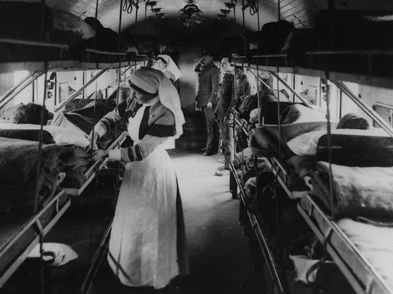 Two nurses tend to wounded inside an ambulance-train ward, France, during World War I. Ambulance trains were used in the main to transport large groups of soldiers to the French coast so that they could return to England for treatment.