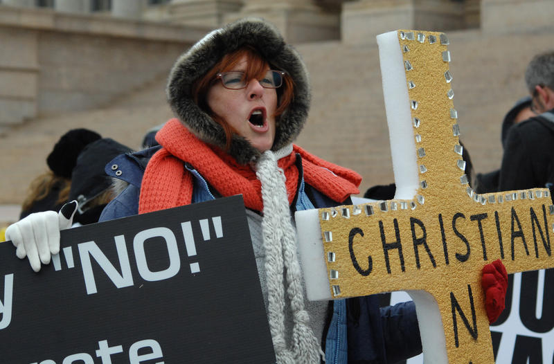An anti-Muslim protester chants Friday on the south steps of the State Capitol building.