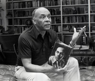 Ralph Ellison in conversation, holding a cigar and a copy of his novel