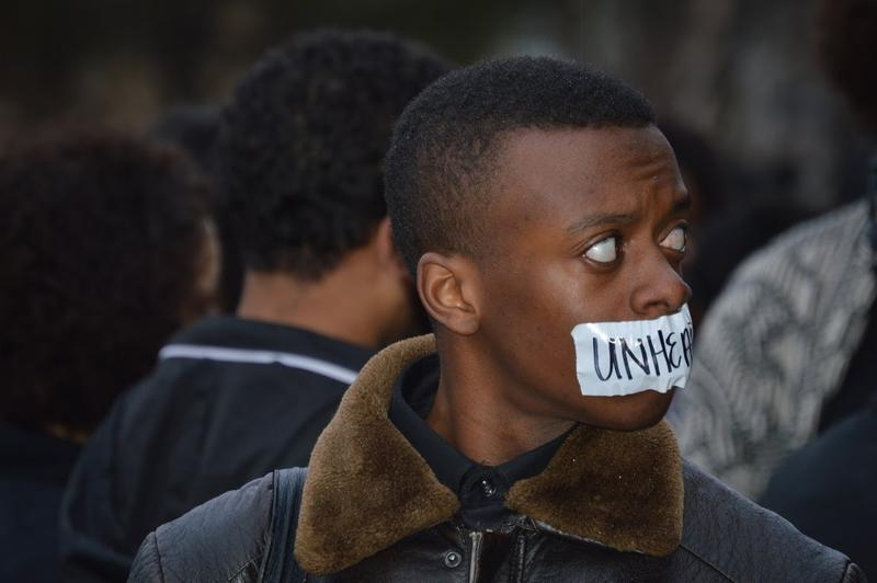 "A protester with tape saying ""Unheard"" over his mouth, a reference to the minority rights student group that organized Monday morning's protest of the Sigma Alpha Epsilon chant video."