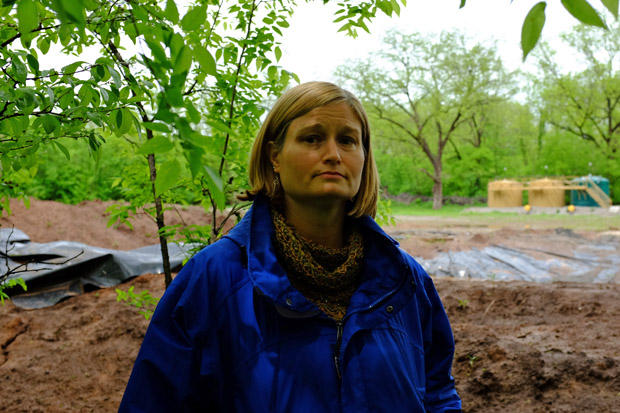 Stillwater resident Tammy Mix stands in front of an oil and gas well behind her house.